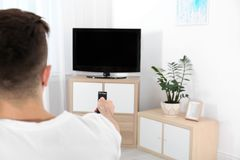 Young man switching channels on modern TV with remote control. At home royalty free stock photography