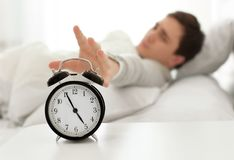 Young man switching off alarm clock signal Stock Photography