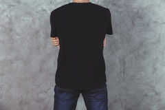 Young man in t-shirt back. Back view of young man in casual black t-shirt and jeans on concrete wall background. Mock up Stock Photography