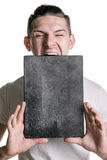 A young man in a T-shirt with a banner for your text or something else, is trying to bite a banner. Vertical frame Royalty Free Stock Image