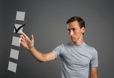 Young man in t-shirt checking on checklist box. Gray background. Stock Photo