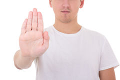 Young man in t-shirt doing a stop symbol isolated on white. Background Royalty Free Stock Images