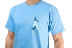 Young man in t-shirt with symbolic blue ribbon. On white background. Cancer awareness concept Stock Photo