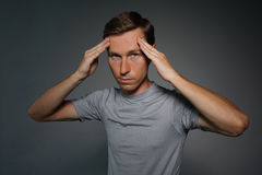 Young man in t-shirt thinking or experiencing headaches. Stock Images