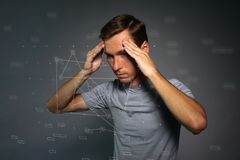 Young man in t-shirt thinking or experiencing headaches. Royalty Free Stock Photos