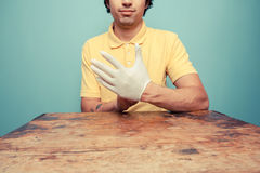 Young man at table putting on rubber glove Royalty Free Stock Photos