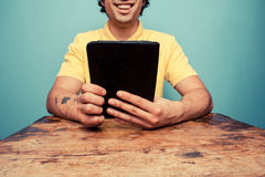Young man at table reading on tablet Stock Photo