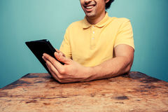 Young man at table reading on tablet Royalty Free Stock Photos