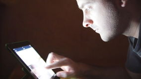 Young man with tablet computer lying on sofa. Guy using tablet computer at home late night. Glowing light on face. He stock video footage