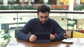 Young man with tablet computer sitting in cafe stock video