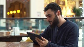 Young man with tablet computer sitting in cafe stock video footage