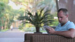 Young man with tablet computer sitting by the city street. stock footage