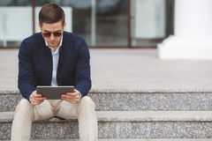 Young man with tablet computer sitting on stairs Stock Images