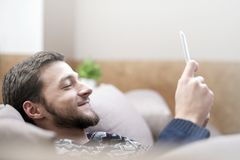 Young man with tablet computer in their hands, on the couch at home. Young positive man with tablet computer in their hands, on the couch at home Stock Photos