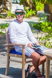 Young man with tablet computer on tropical beach Stock Image