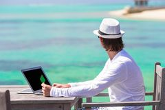 Young man with tablet computer on tropical beach Royalty Free Stock Photos