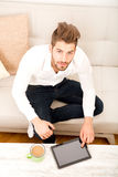 Young man with tablet on couch Royalty Free Stock Image