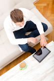 Young man with tablet on couch Stock Photo
