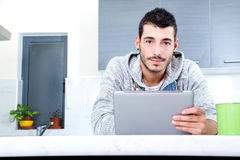 Young man with tablet in the kitchen Royalty Free Stock Photography
