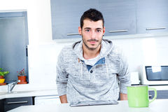 Young man with tablet in the kitchen Stock Photography