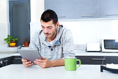 Young man with tablet in the kitchen Stock Photos
