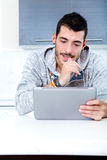 Young man with tablet in the kitchen Stock Images