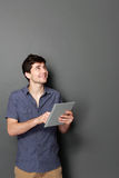Young man with tablet looking up to copy space Stock Images