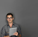 Young man with tablet looking up to copy space Royalty Free Stock Images