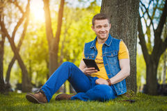 Young man with tablet in the park Royalty Free Stock Photography