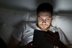 Young man with tablet pc in bed at home bedroom Stock Image
