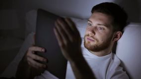 Young man with tablet pc in bed at home bedroom stock video footage