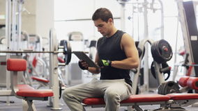 Young man with tablet pc computer in gym stock video footage