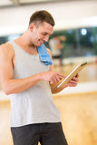Young man with tablet pc computer and towel in gym. Fitness, sport, training, gym, technology and lifestyle concept - young man with tablet pc computer and towel Stock Photo
