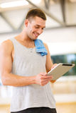 Young man with tablet pc computer and towel in gym. Fitness, sport, training, gym, technology and lifestyle concept - young man with tablet pc computer and towel royalty free stock image