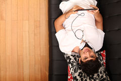 Young man with a Tablet PC and Headphones on the Sofa Royalty Free Stock Images