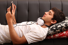 Young man with a Tablet PC and Headphones on the Sofa Stock Image