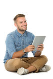 Young man with a tablet pc smile while sitting on the floor Royalty Free Stock Photo