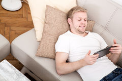 Young man with a Tablet PC on the Sofa Stock Photography