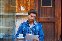 Young man with tablet pc touch in an cafe Stock Image