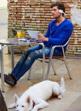 Young man with tablet pc touch with dog. Young man with tablet pc touch in an cafe outdoor sitting with dog and headphones Stock Images