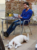 Young man with tablet pc touch with dog. Young man with tablet pc touch in an cafe outdoor sitting with dog and headphones Stock Photography