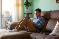 Young man with tablet on sofa at home stock photos