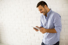 Young man with tablet standing by white wall Stock Images