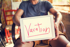 Young man with a tablet with the text vacation Royalty Free Stock Image