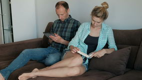Young man with tablet and woman reading book sitting on sofa indoors. Husband and wife spend time on comfortable sofa in apartment, doing their own things stock footage