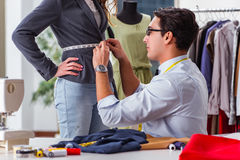 The young man tailor working with female client. Young man tailor working with female client Stock Image