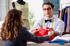 The young man tailor working with female client. Young men tailor working with female client Stock Photography