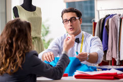 The young man tailor working with female client. Young men tailor working with female client Royalty Free Stock Image
