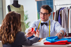 The young man tailor working with female client. Young men tailor working with female client Stock Images