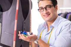 The young man tailor working on new clothing Royalty Free Stock Images